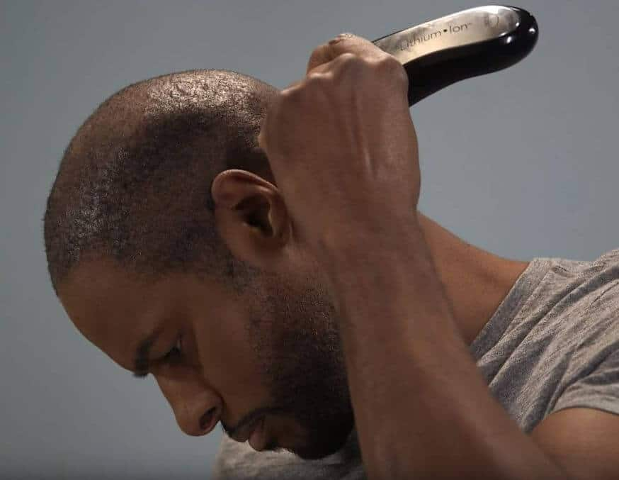 A man using Wahl professional hair clippers to style his hair.