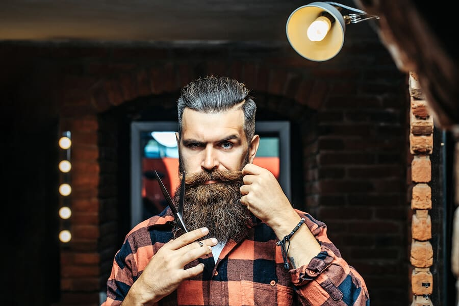 Handsome bearded man hipster with stylish haircut and beard holding scissors in red checkered shirt near mirror with serious face in beauty salon or barbershop as barber near brick wall